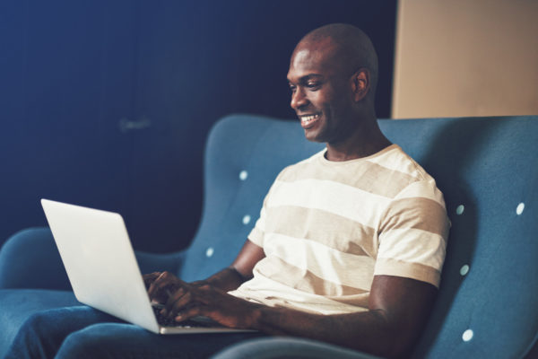 Smiling young African male entrepreneur browsing online with a laptop while sitting on a sofa working from home